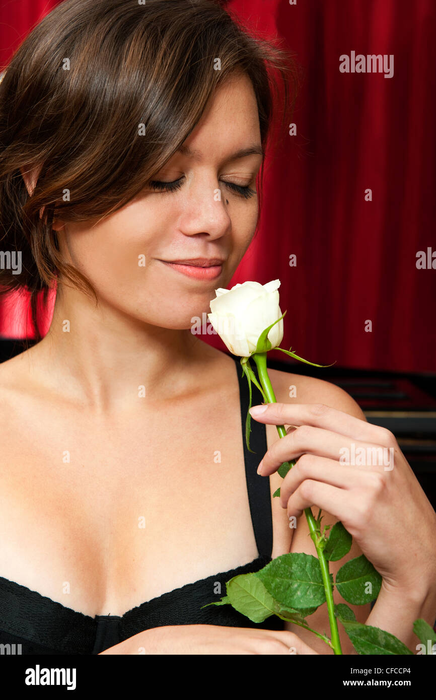 Beautiful young woman picking up the scent of a rose, with an introvert smile on her face - Stock Image
