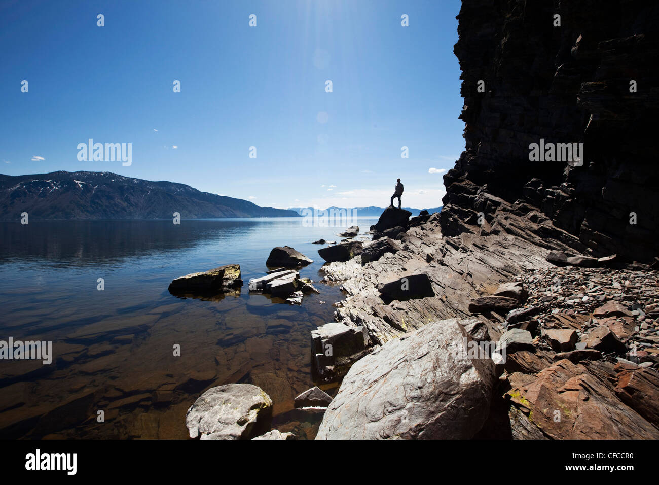 A male figure stands on a rock at the edge of a beautiful lake on a sunny day in Idaho. - Stock Image