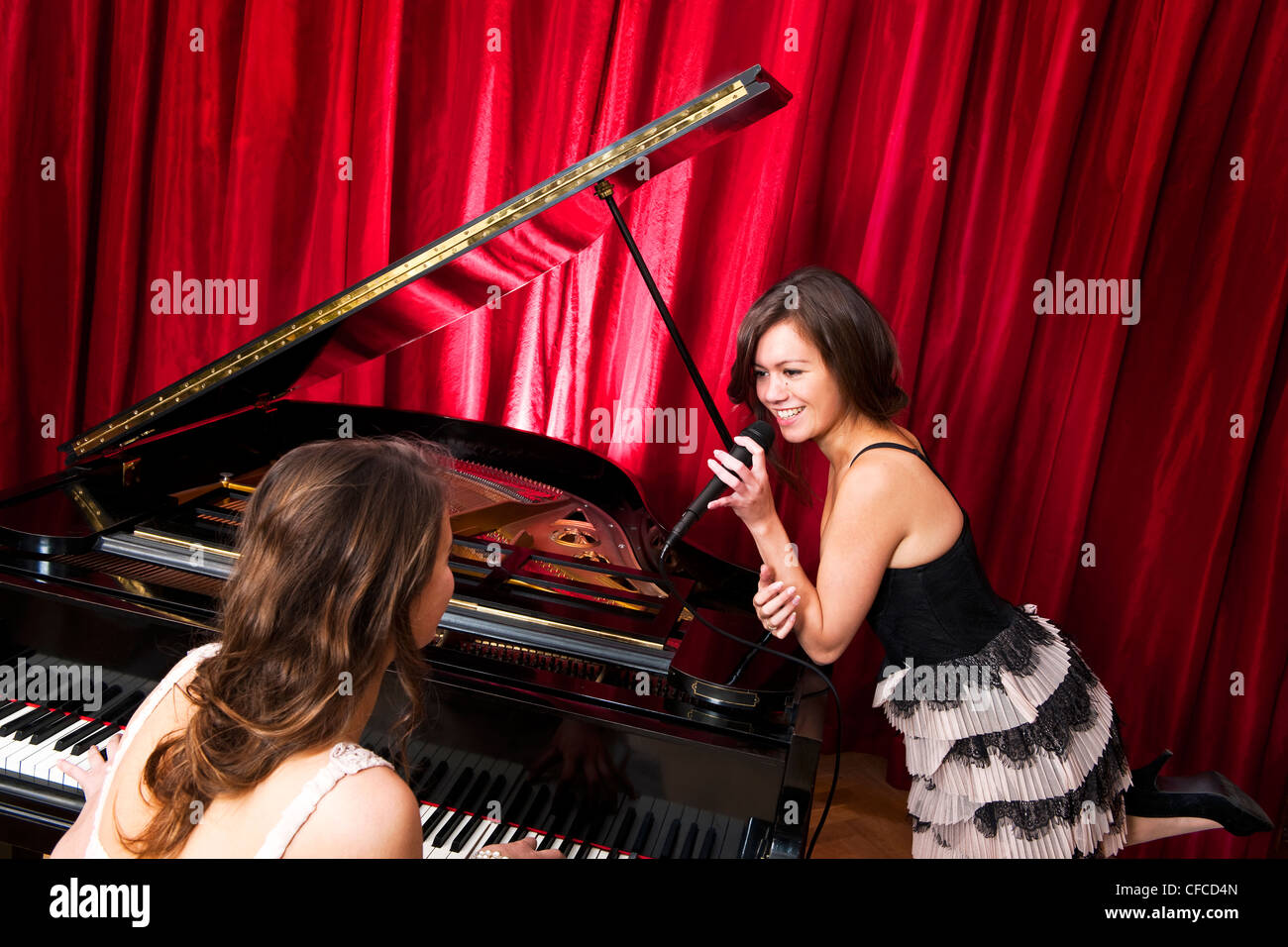 Two women singing a duet with a concert piano - Stock Image