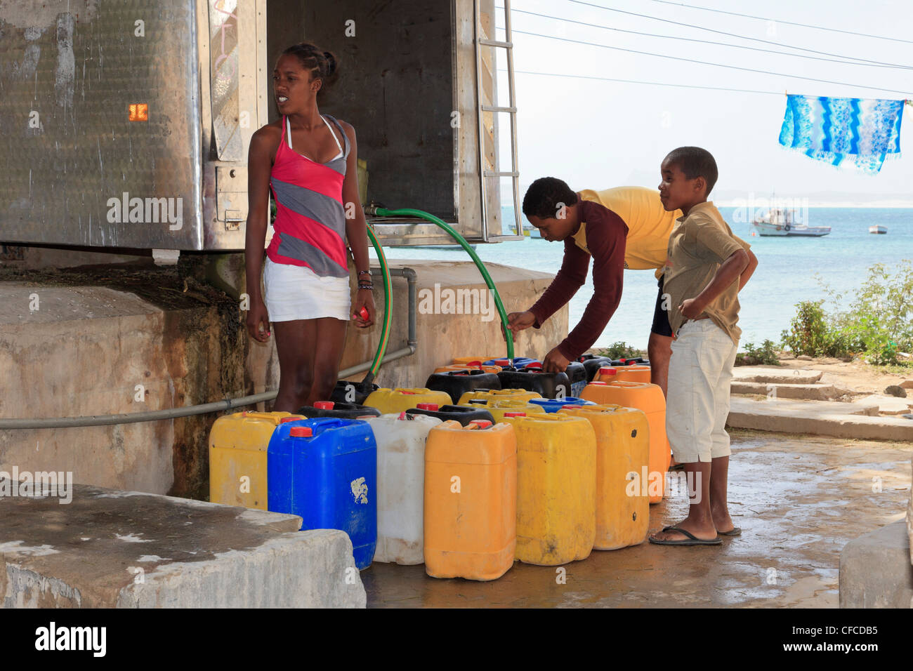 Sal Rei, Boa Vista, Cape Verde Islands. Local people with containers for collecting desalinated drinking water from - Stock Image