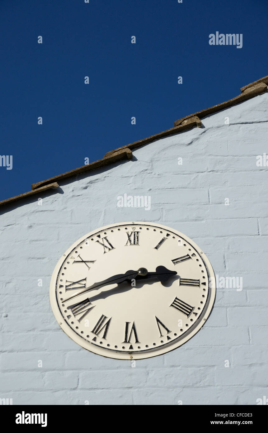 Outside clock with roman numerals mounted on blue wall, UK - Stock Image