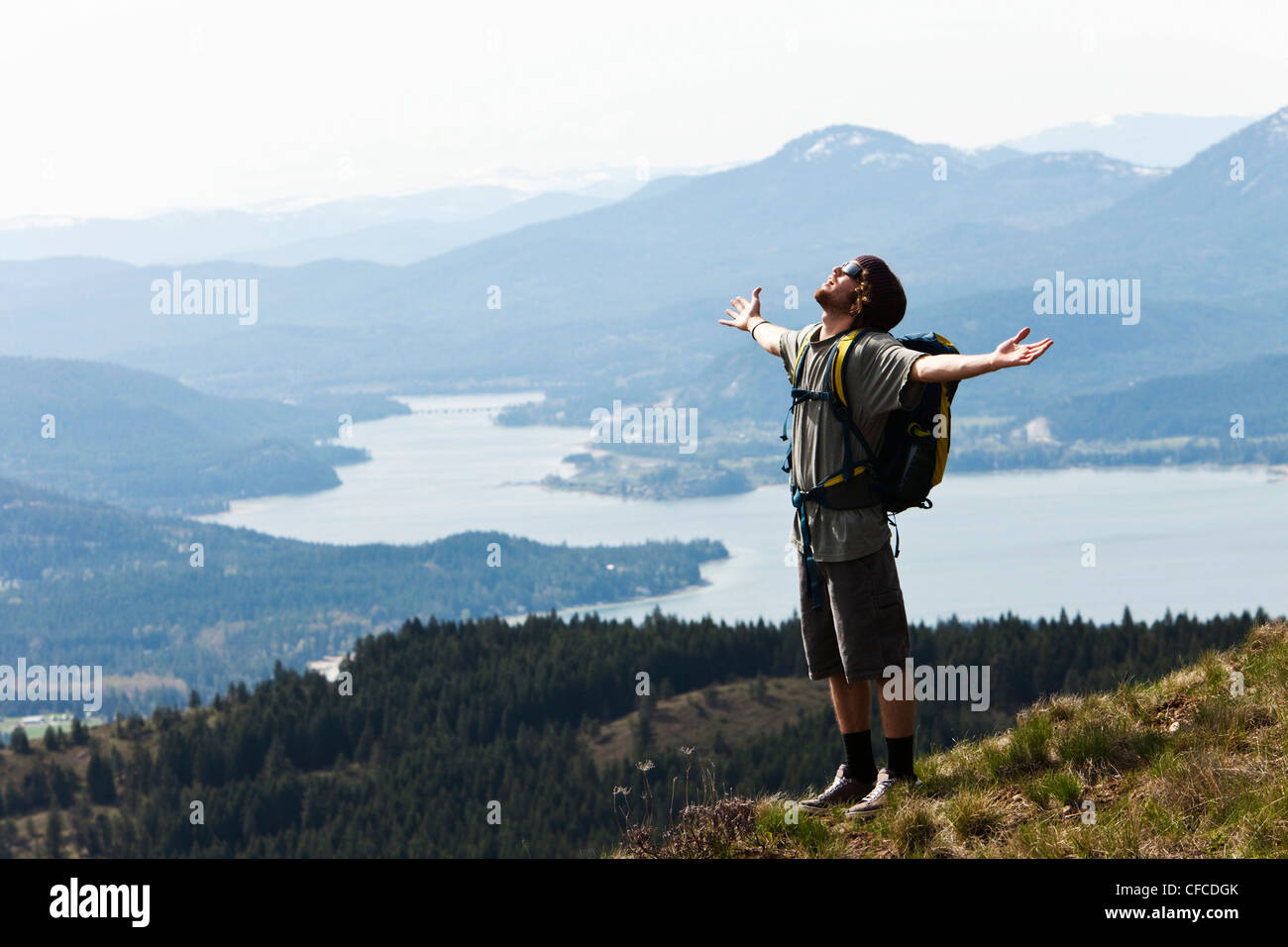 A young man holds his arms open in success after hiking to the top of a mountain in Idaho. - Stock Image