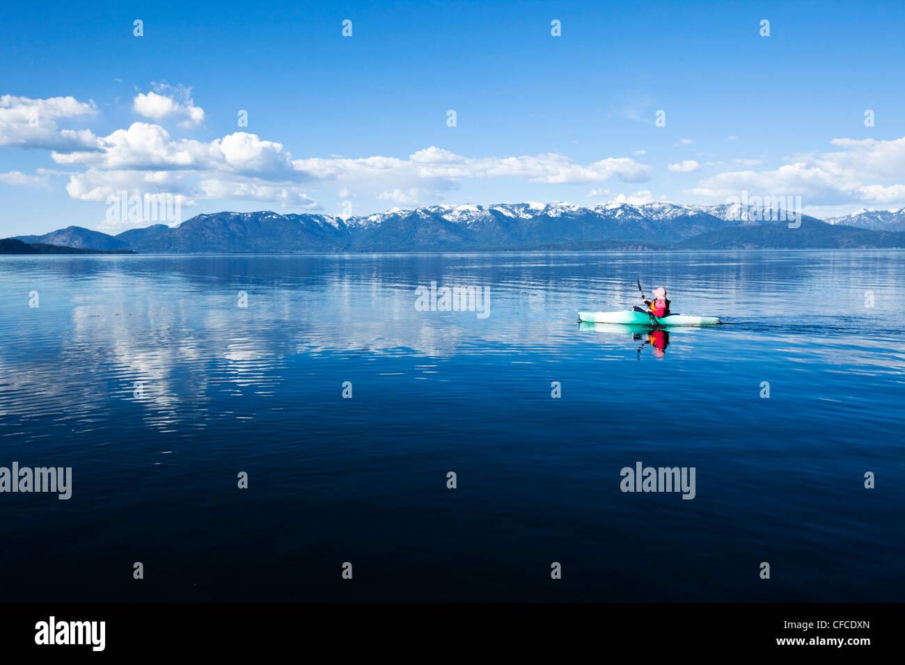An adventurous women kayaking across a huge calm lake in Idaho. - Stock Image