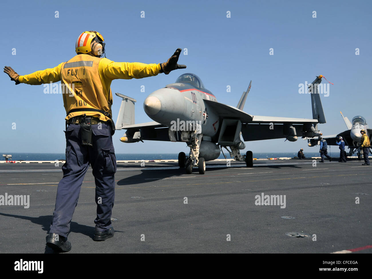 ARABIAN SEA (March 5, 2012) Aviation Boatswain's Mate (Handling) 2nd Class Derrick Williams directs an F/A-18E - Stock Image