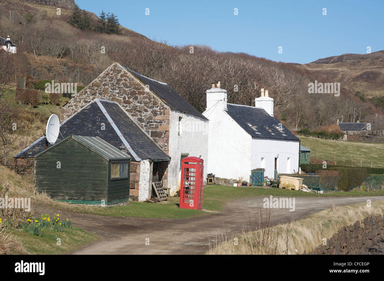 The Post Office, green hut in the foreground, and a red phone box on the Isle of Canna. Inner Hebrides, Scotland. - Stock Image