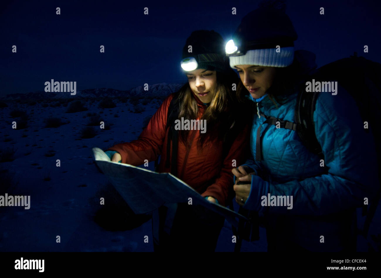 Two women look over a map in the early morning before hiking in the Sierra Foothills outside of Lake Tahoe, California. - Stock Image