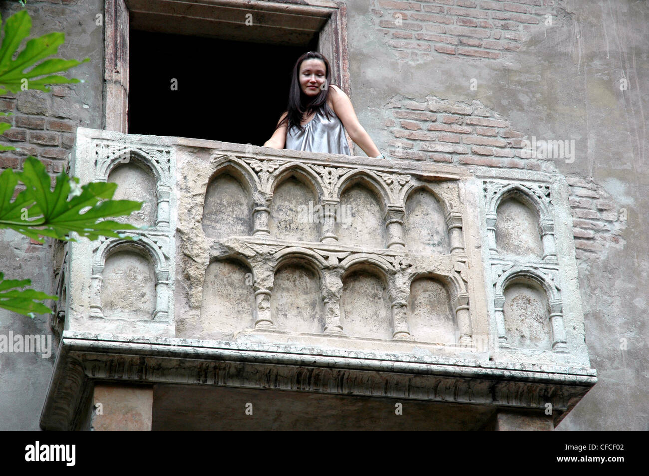 A  young woman poses, Juliet  like, on the famous balcony in Verona Italy - Stock Image