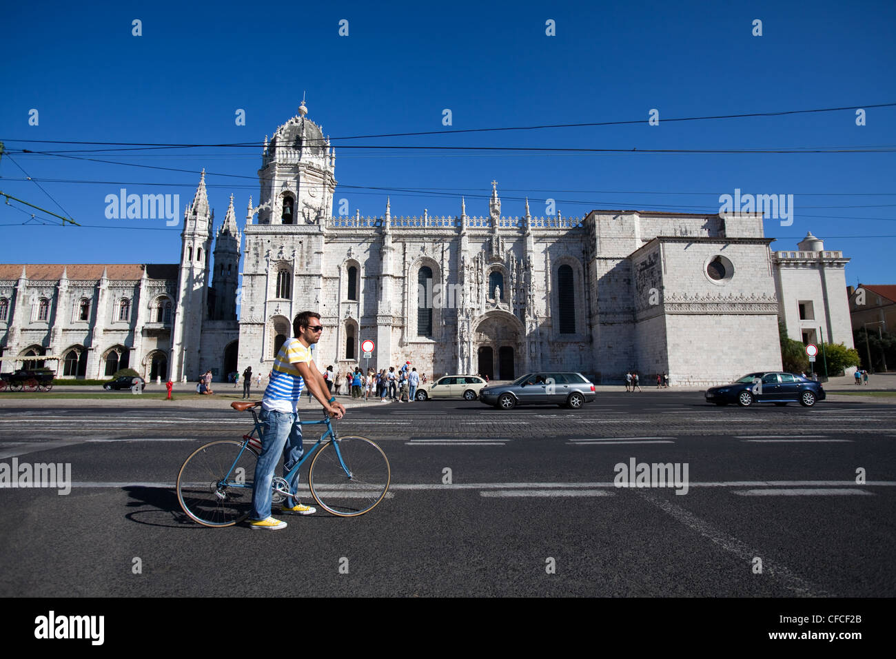 A cyclist standing in front of the Jeronimos Monastery in Lisbon, Portugal. - Stock Image