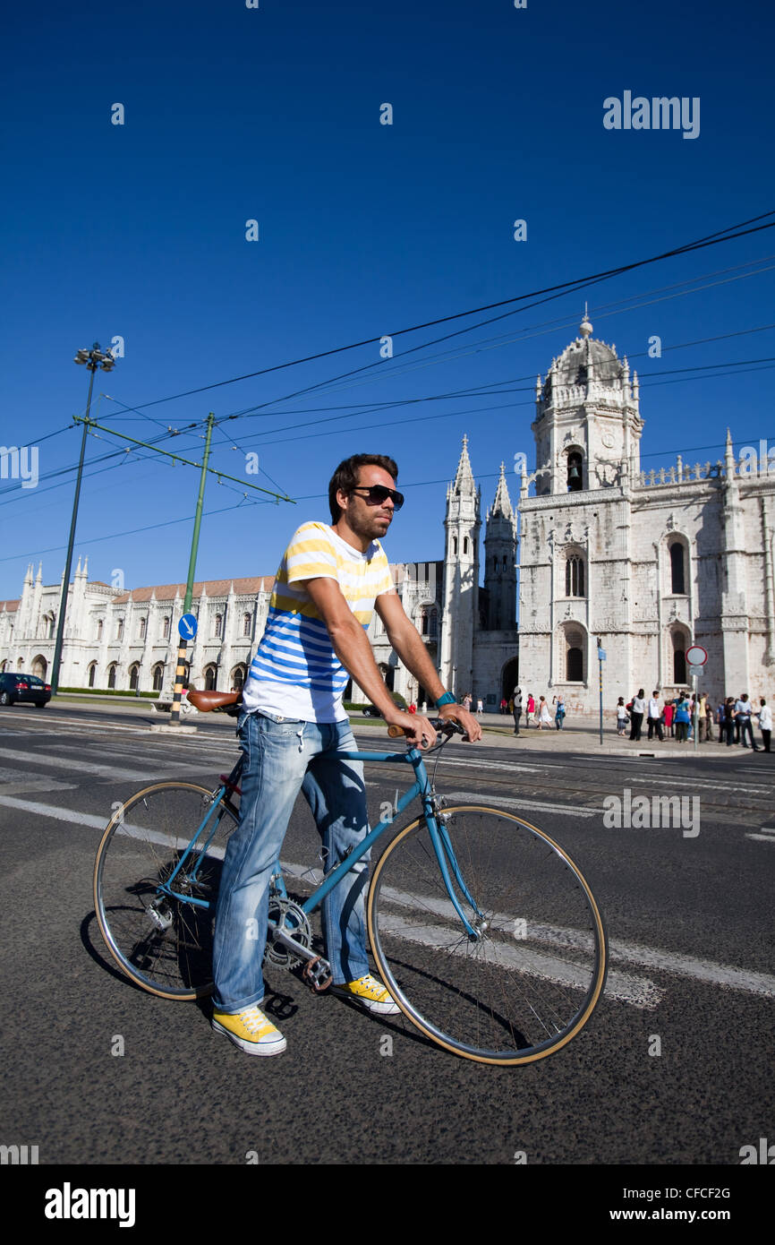 A cyclist standing in front of Jeronimos Monastery in Belem, Lisbon, Portugal. - Stock Image