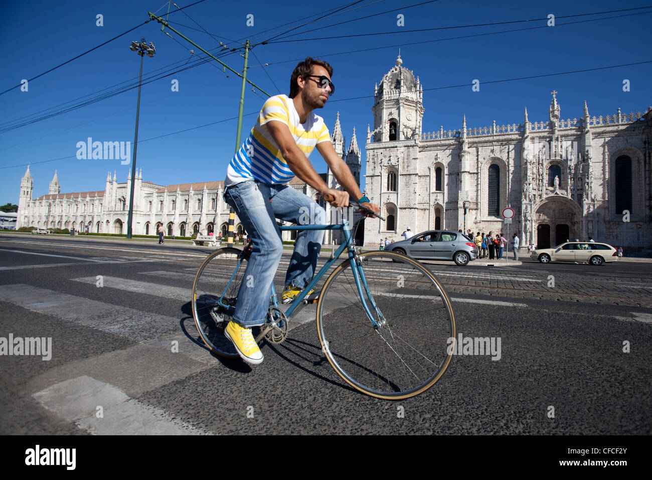 A cyclist rides next to Jeronimos Monastery in Lisbon, Portugal. - Stock Image