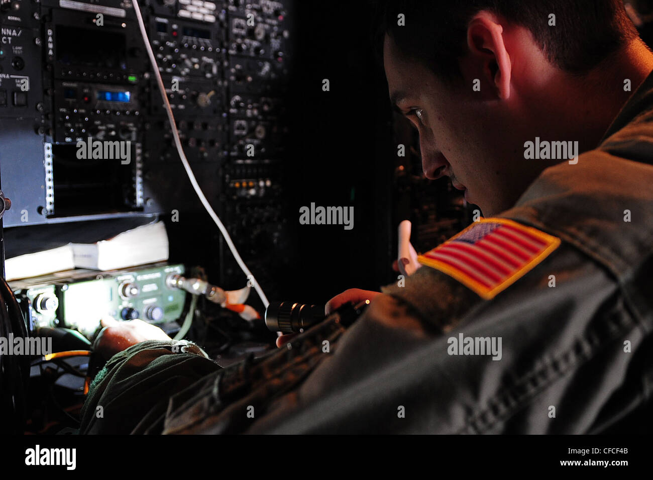 A U.S. Air Force aerial communications engineer programs a radio aboard an MC-130E aircraft prior to a mission during - Stock Image