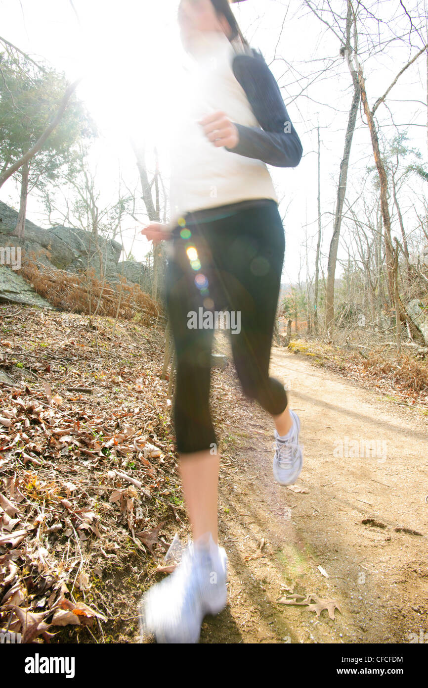 Athletic female running on a trail in the woods during winter. - Stock Image