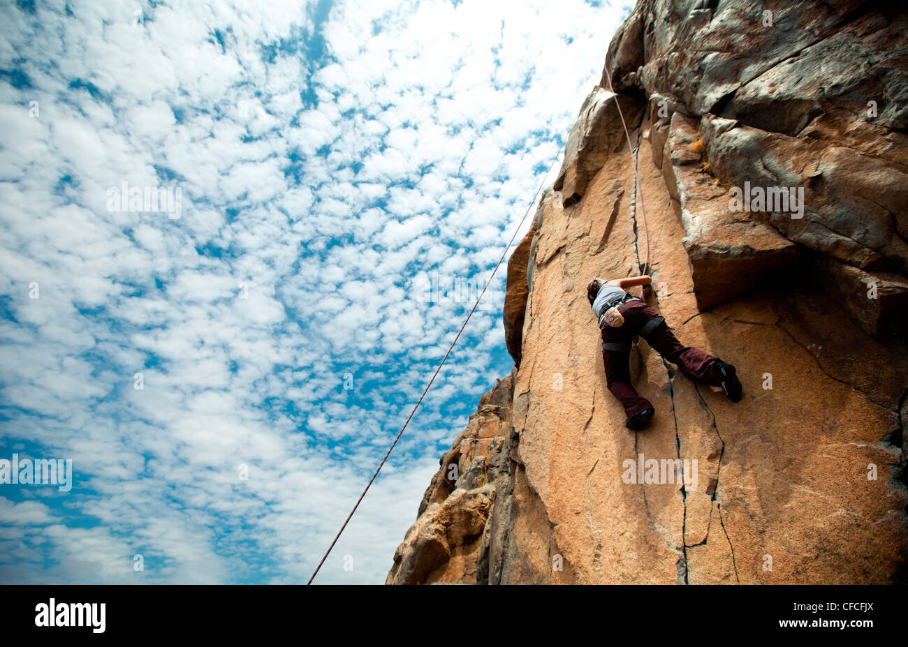 Looking up at a woman climber a crack seam in a granite cliff face. Stock Photo