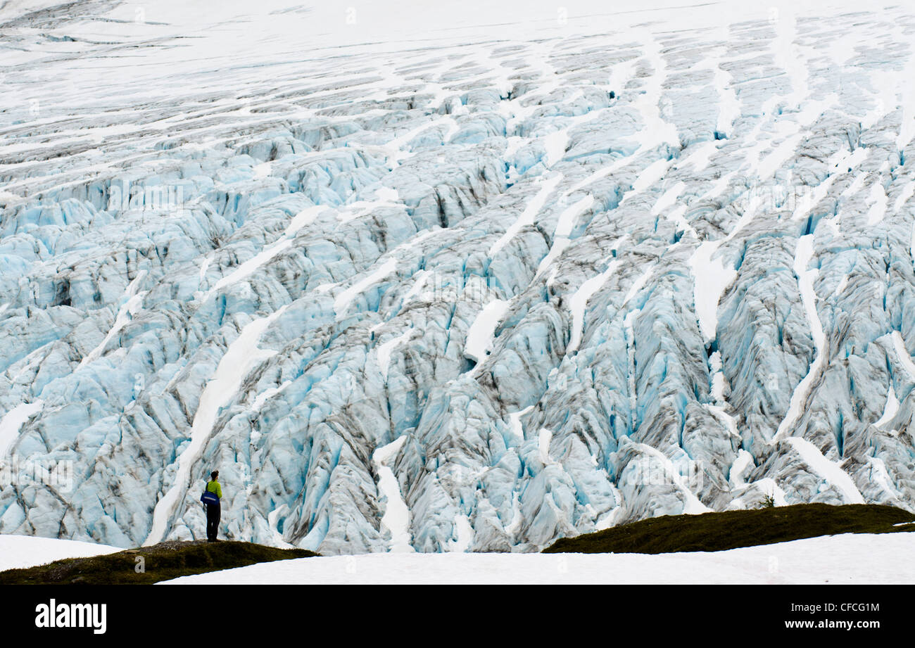 A young man stands in wonder in front of the Exit Glacier in Seward, Alaska. - Stock Image