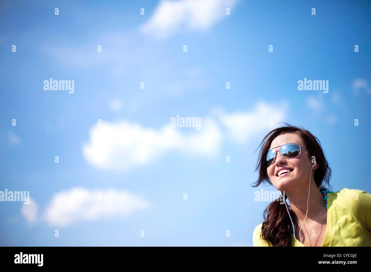 A young woman looks off smiling while listening to music. - Stock Image