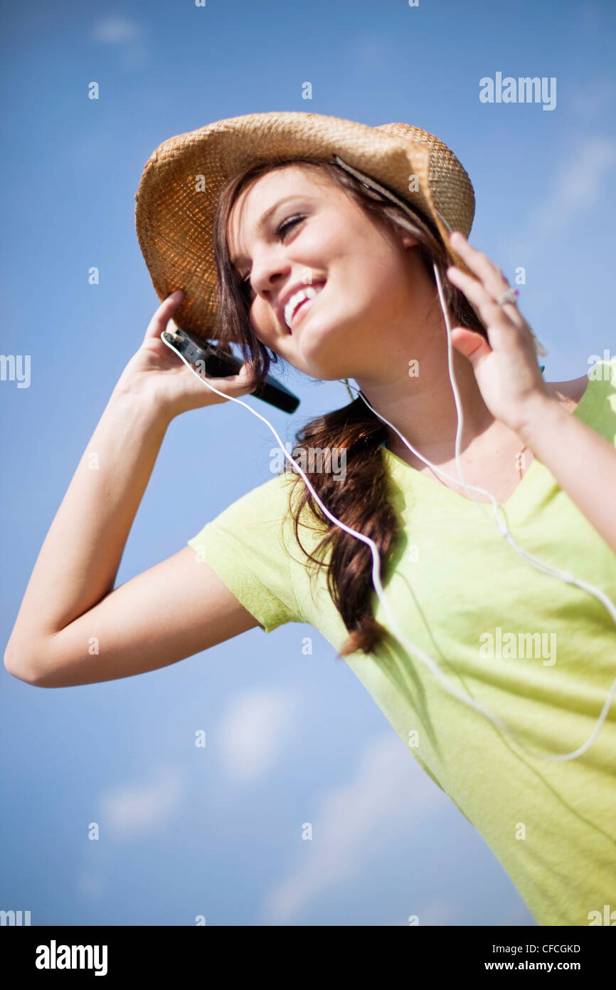 A young woman smiles while listening to music. - Stock Image