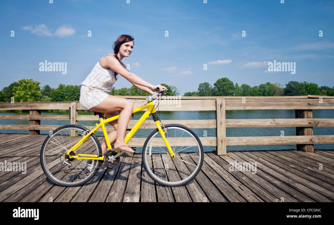 A young girl rides a yellow bike down a pier. - Stock Image