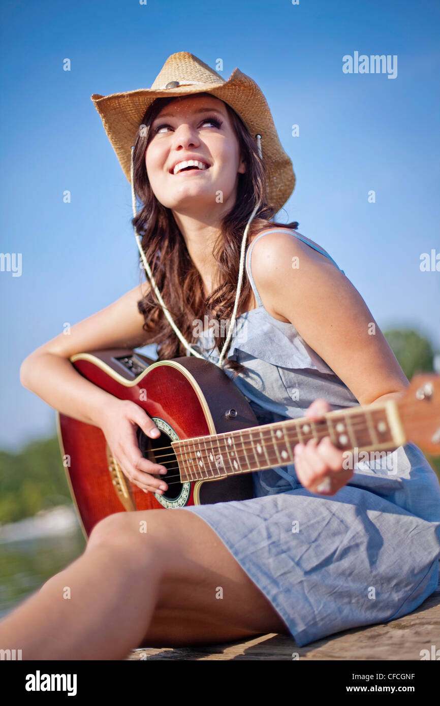 A young woman sits on a pier playing guitar. - Stock Image