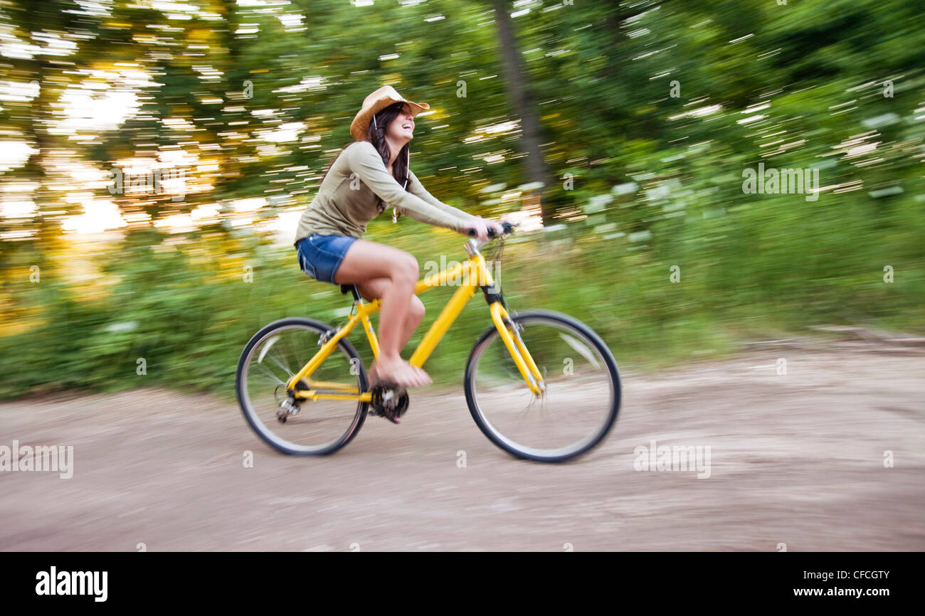 a young woman rides a yellow bike down a dirt road. - Stock Image