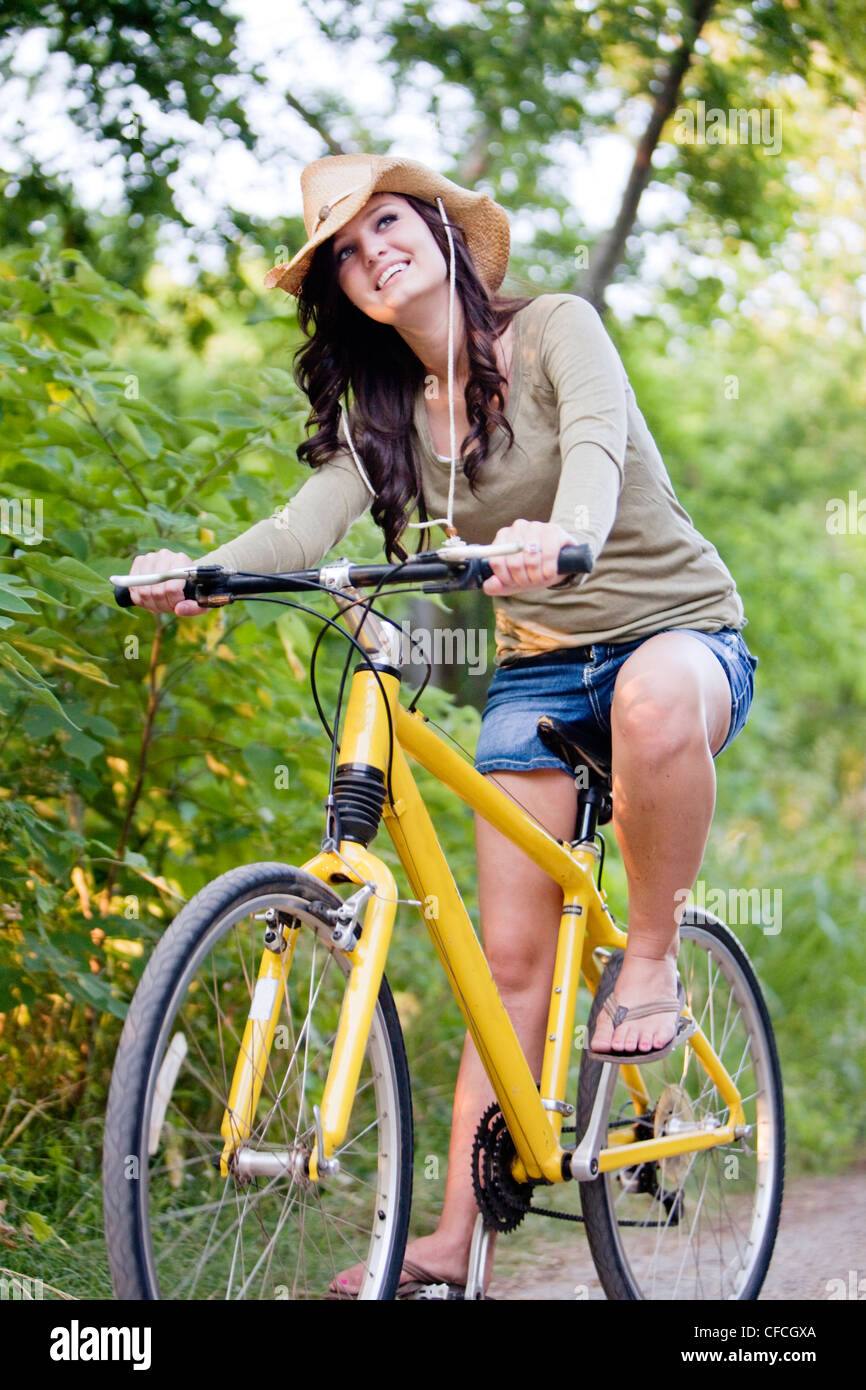 A smiling young woman rides a yellow bike down a dirt road. - Stock Image