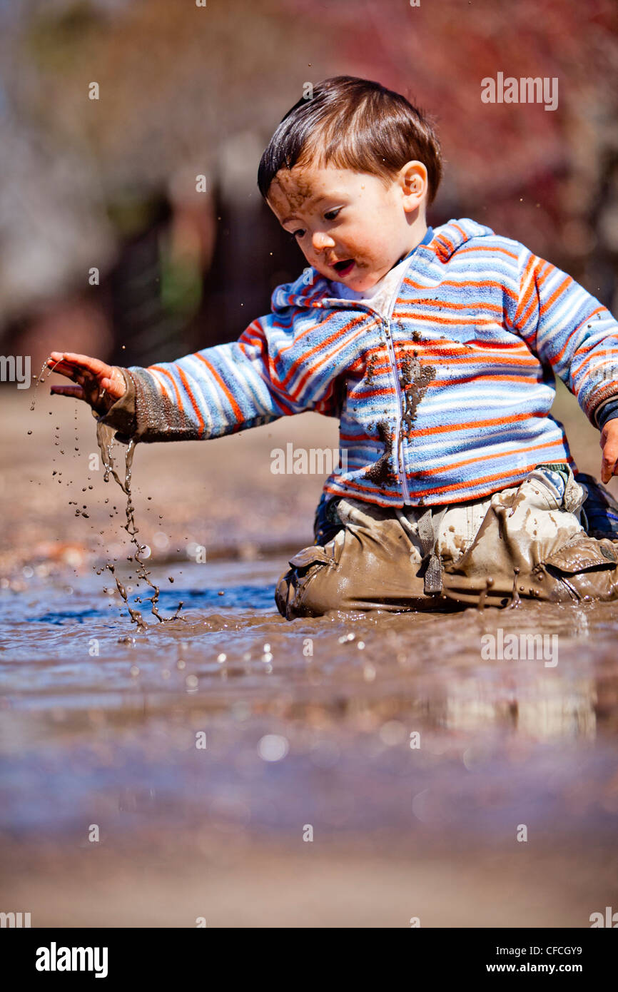 a two year old boy, plays in a mud puddle. - Stock Image