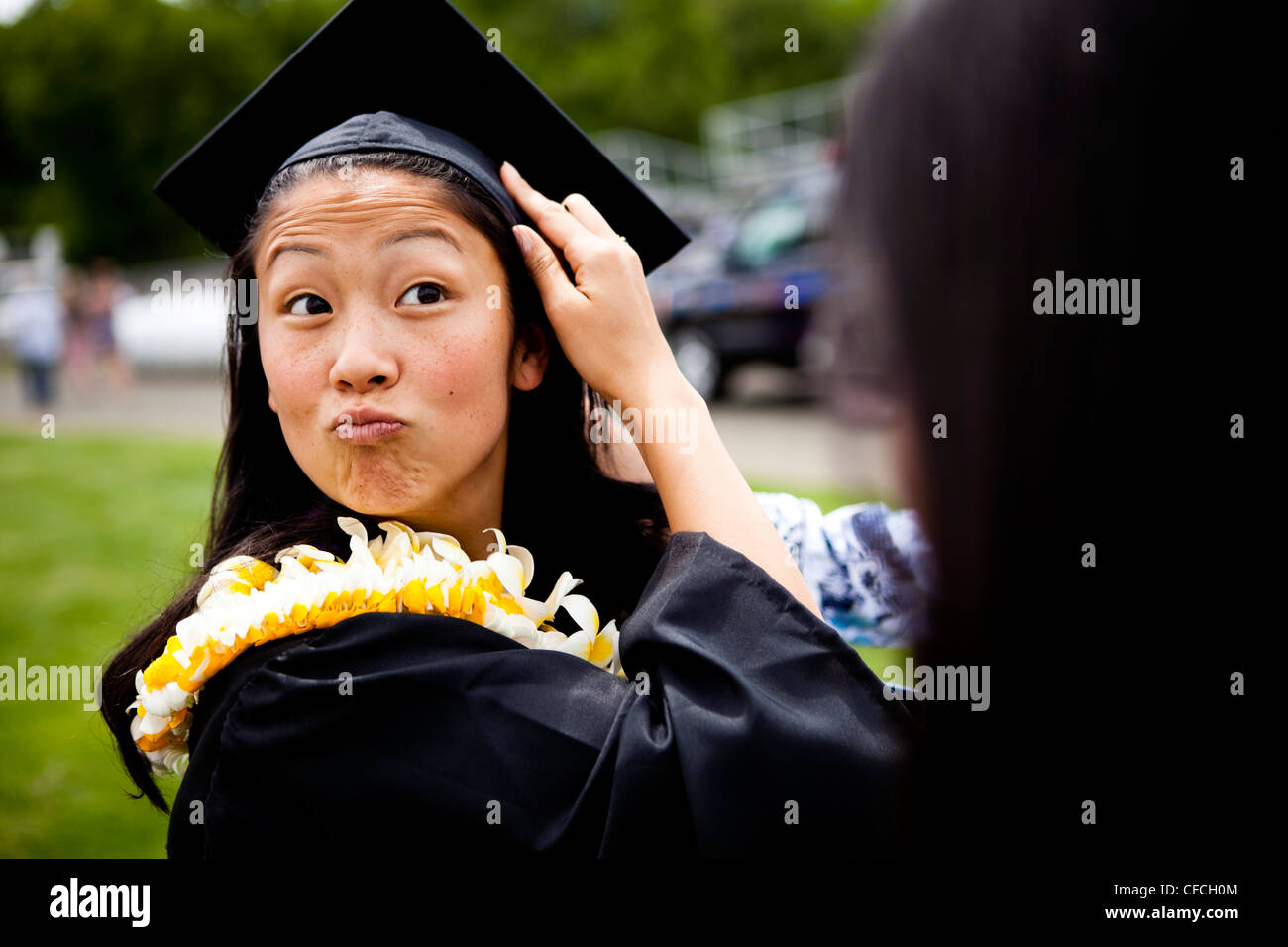 a graduate makes funny faces while she is shrouded in Hawaiian Leis (lays) on her graduation day from the University - Stock Image