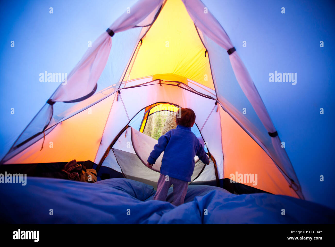 a little boy opens and closes the zippered tent door while he stand on a blue sleeping bag. The tent is orange and - Stock Image