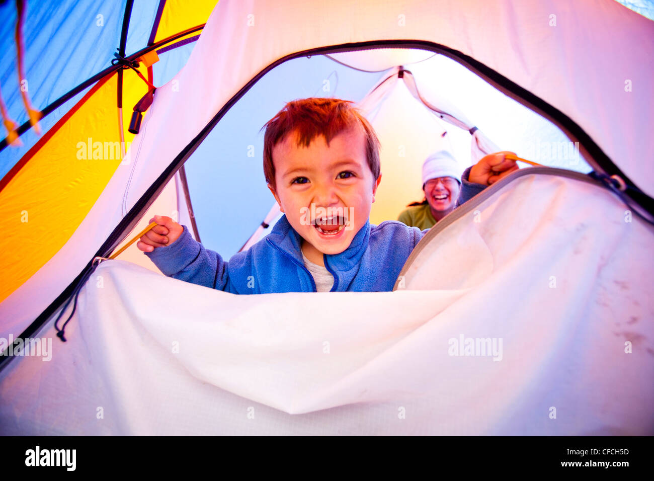 a little boy opens and closes the zippered tent door while he stands on a blue sleeping bag. The tent is orange - Stock Image