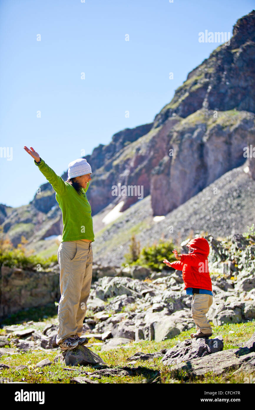 a mother waves her hands up in the air while she walks with her 2 year old son through an alpine meadow with wildflower. - Stock Image