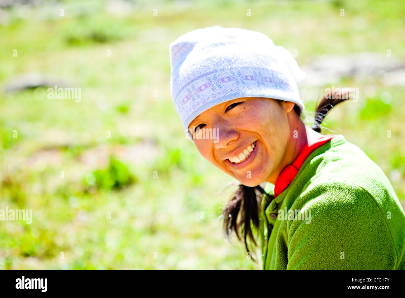 a woman smiles as she sits in an alpine meadow. She is just off the Continental Divide Trail (CCT, trail number - Stock Image