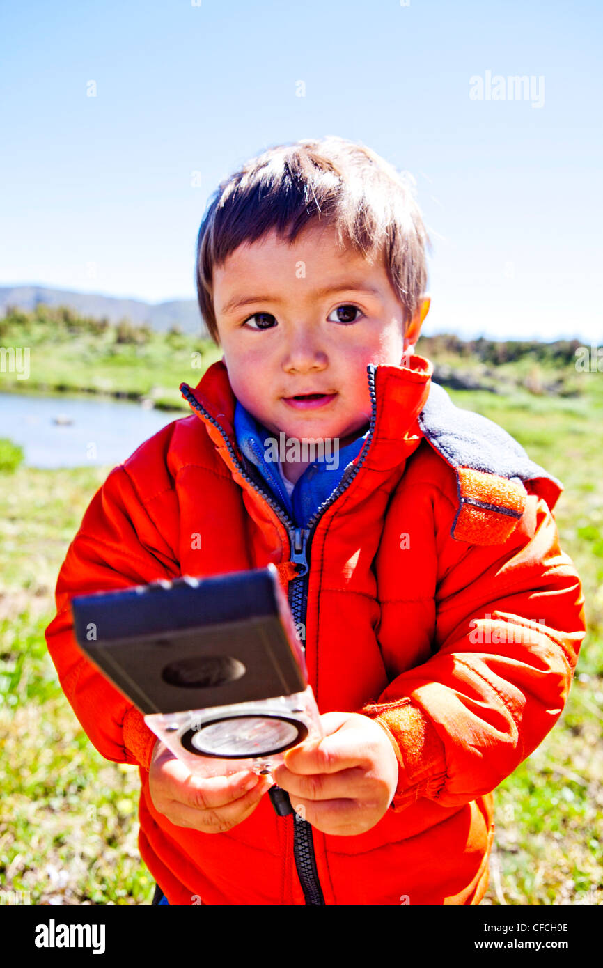 a 2 year old, holds a compass while standing in an alpine meadow with alpine lake in the background. He is just - Stock Image
