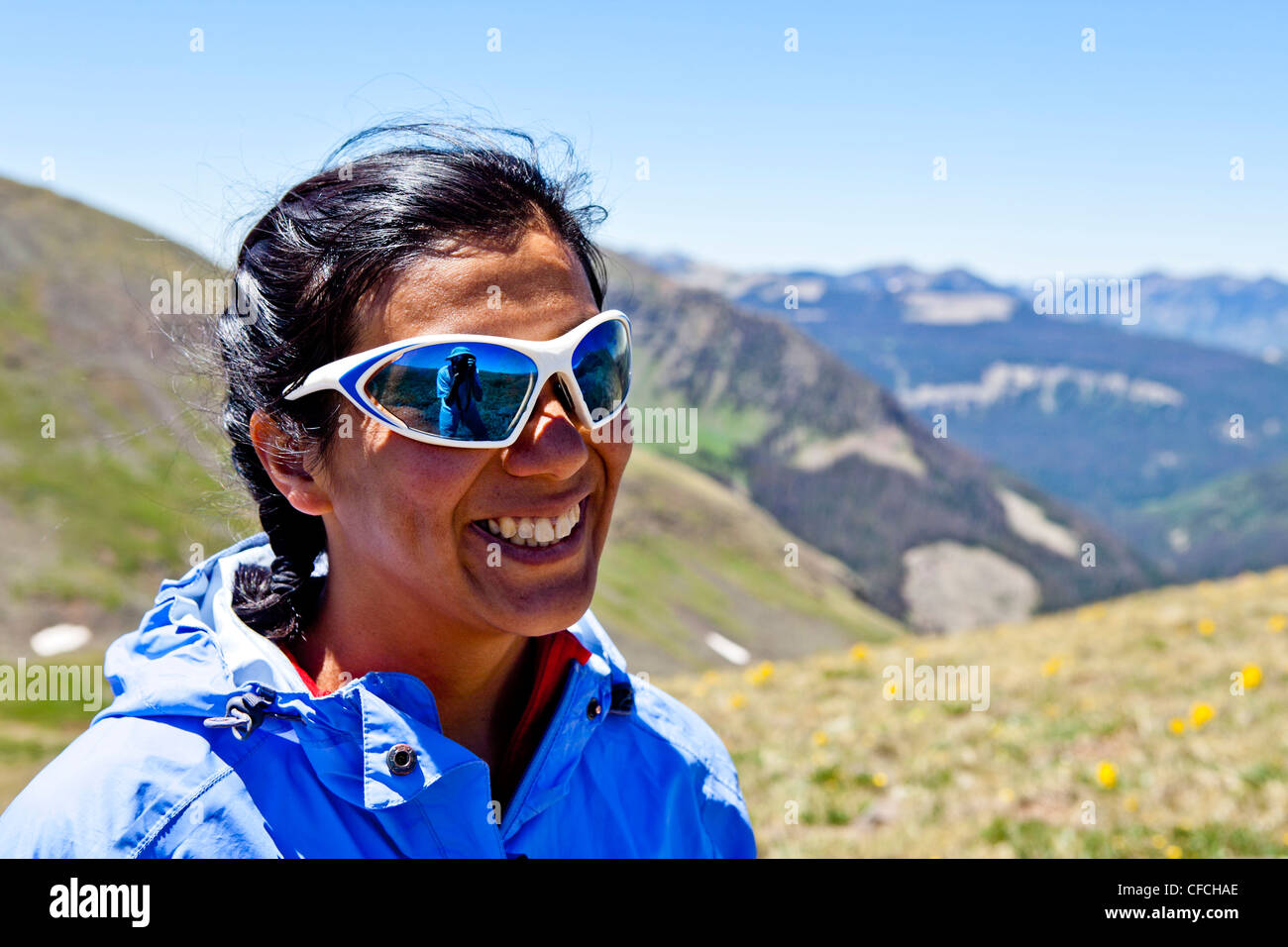 a woman smiles while vistas of the Rocky Mountains are behind her. She is on the Continental Divide Trail (CCT, - Stock Image