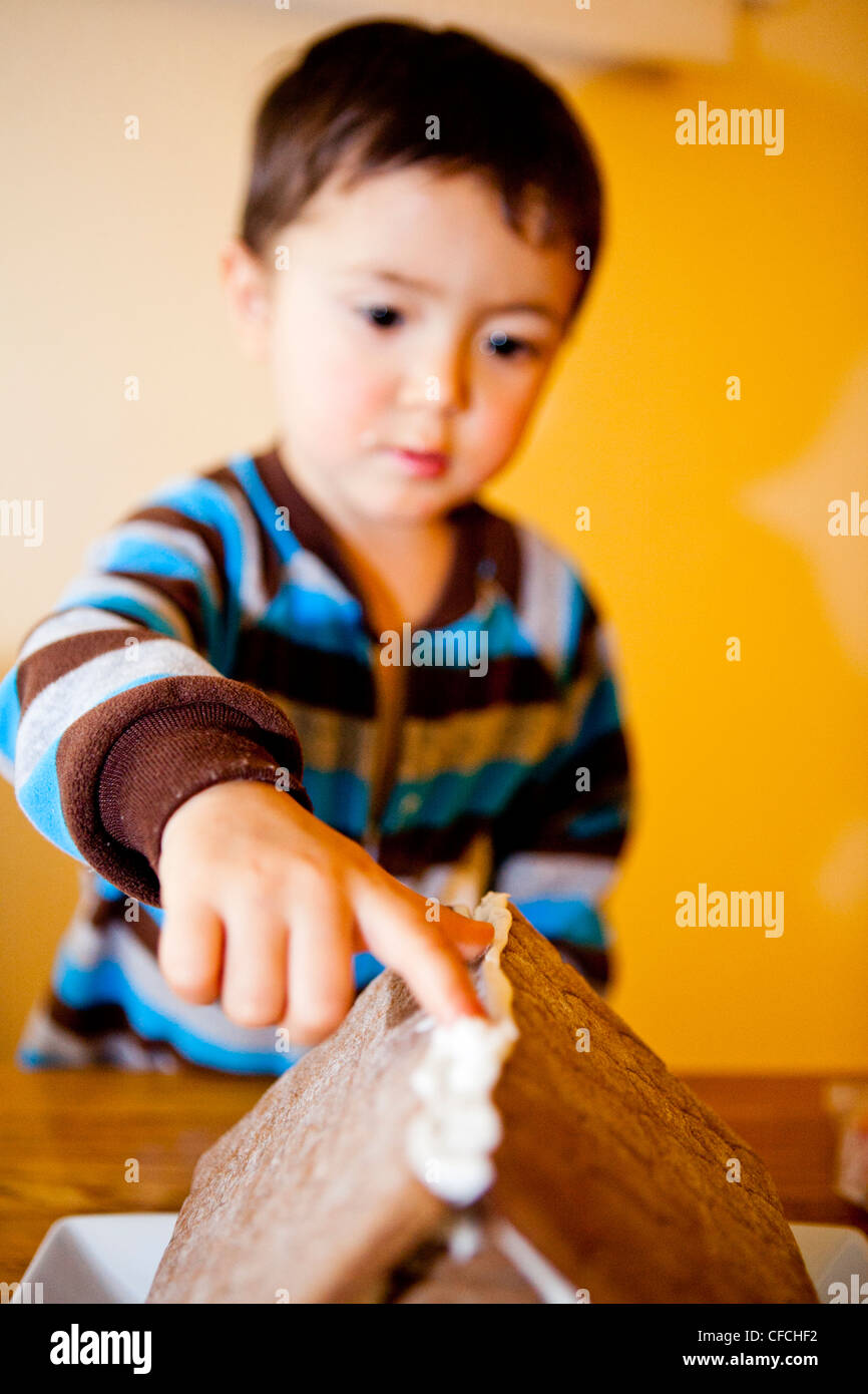 a two and half year old boy (2.5), makes a ginger bread house. - Stock Image