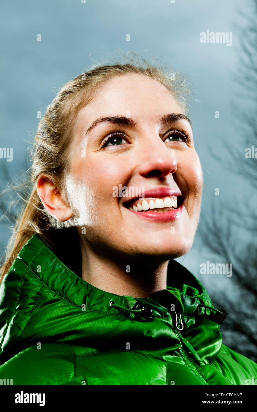 Environmental Portrait of a young woman standing on a running trail in a green jacket in the winter time. - Stock Image