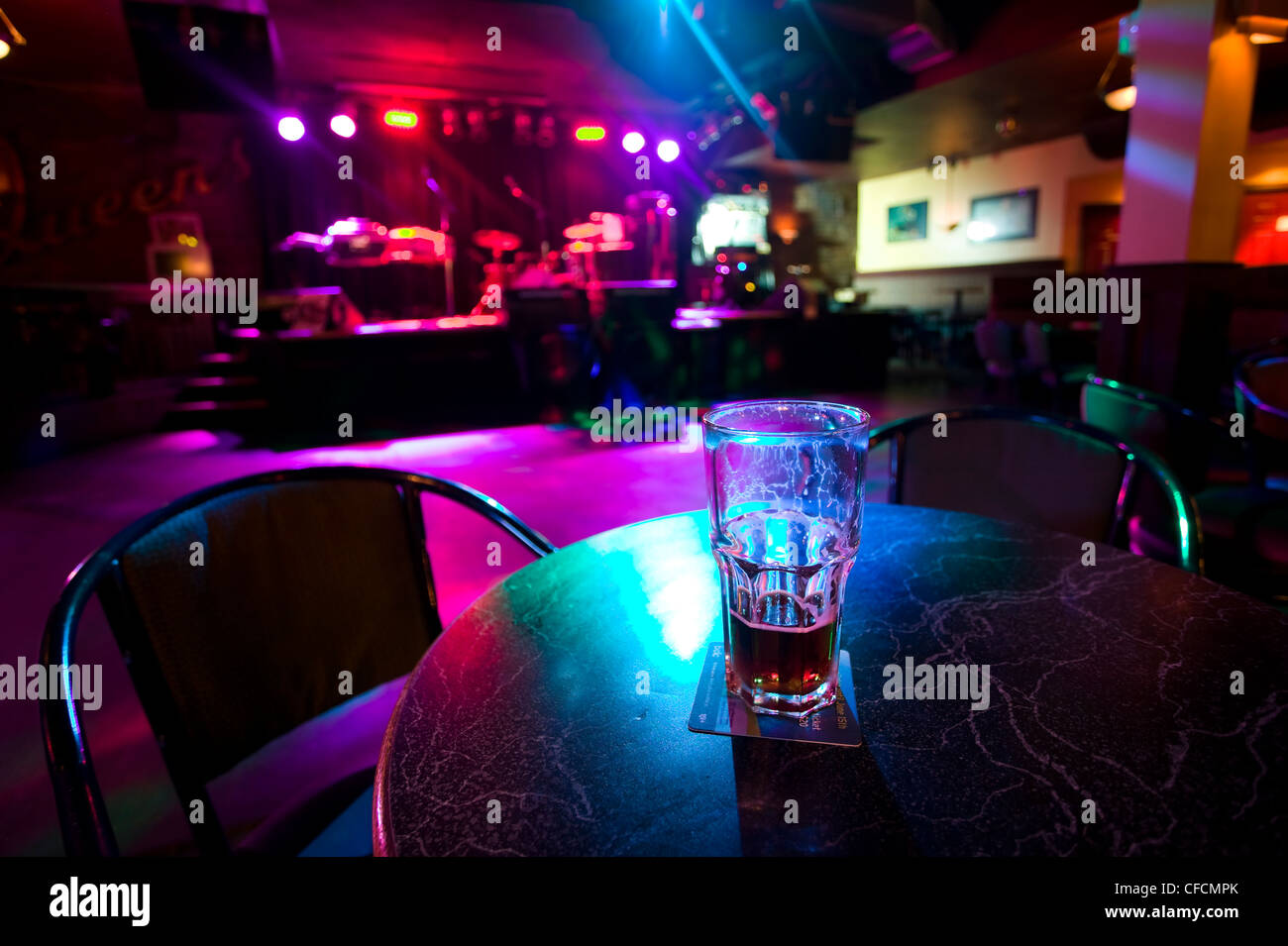 A Half Empty Beer Glass Sits On A Table Of A Nightclub
