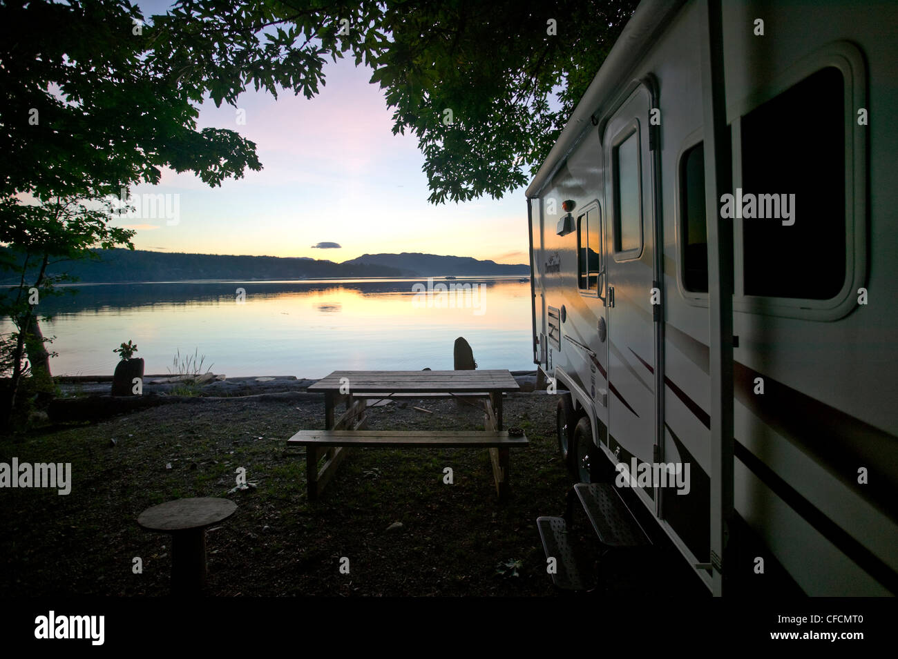 A camper at sunset reflects the last rays of light over Rebecca Spit on Quadra Island, British Columbia, Canada. - Stock Image