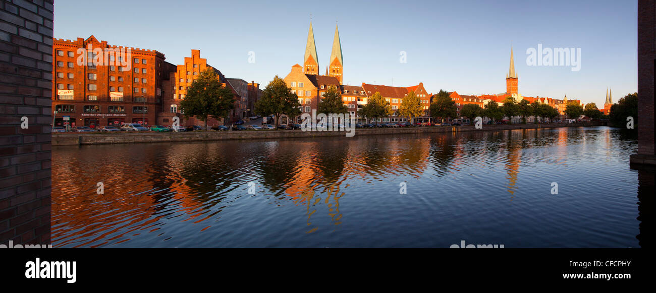 Panoramic view over the Trave river to the old town of Luebeck with old storehouses at the Holsten harbour, St Mary´s - Stock Image