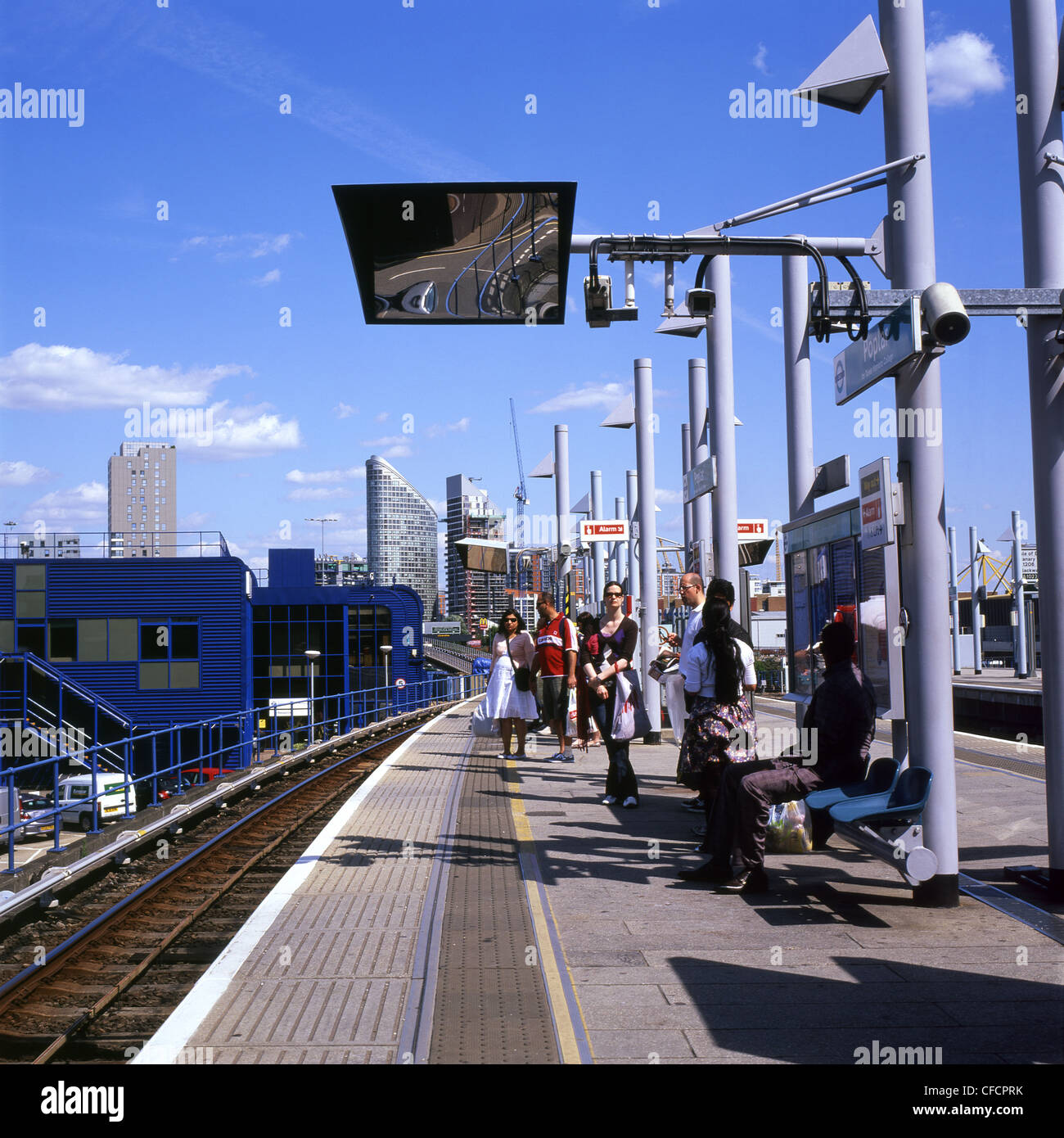 People waiting for an overground DLR train in summer on the platform at Poplar Station London England UK - Stock Image