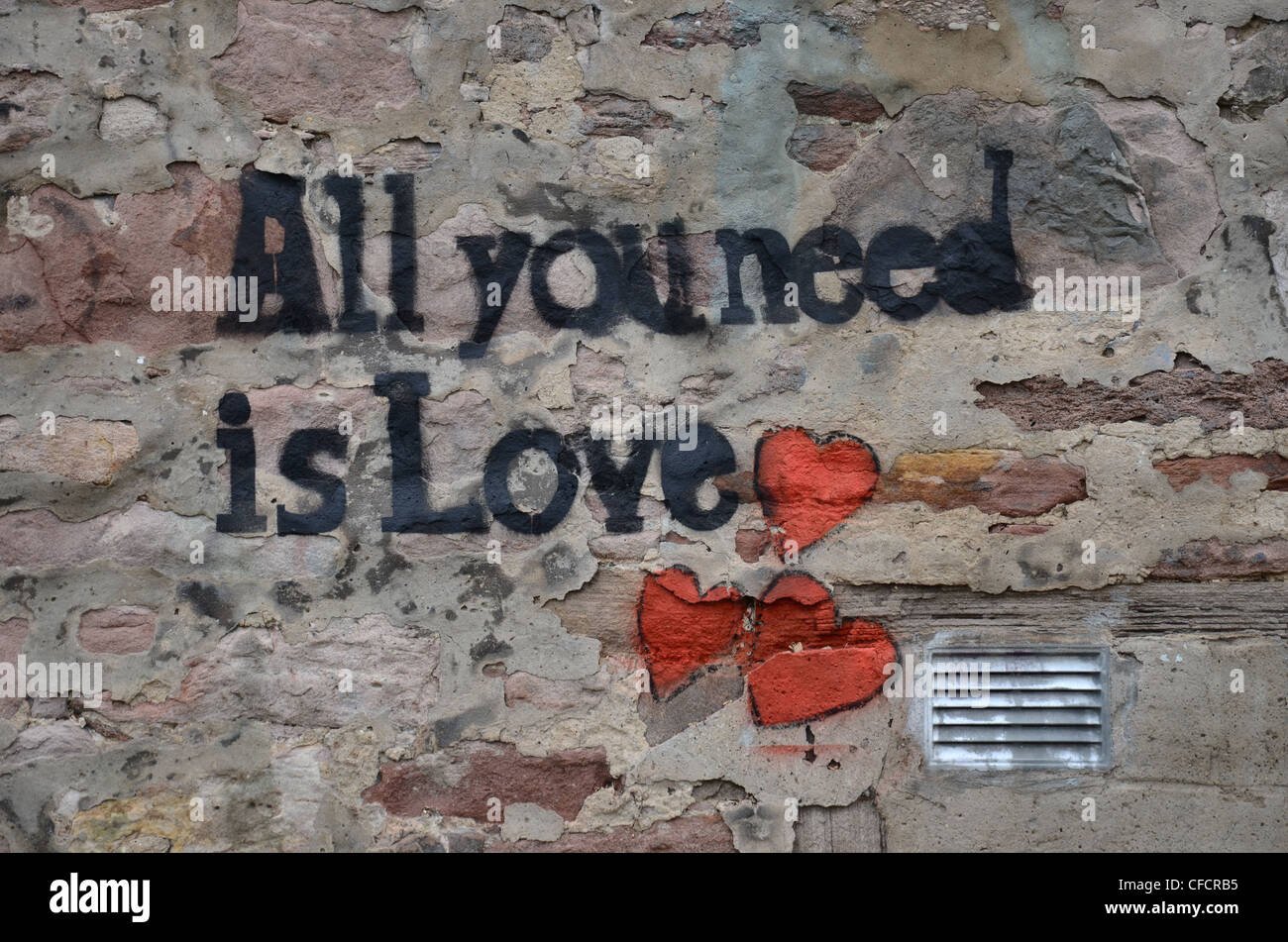 """""""All You Need Is Love"""" graffiti on a wall in Edinburgh and the title of a Beatles song. Stock Photo"""