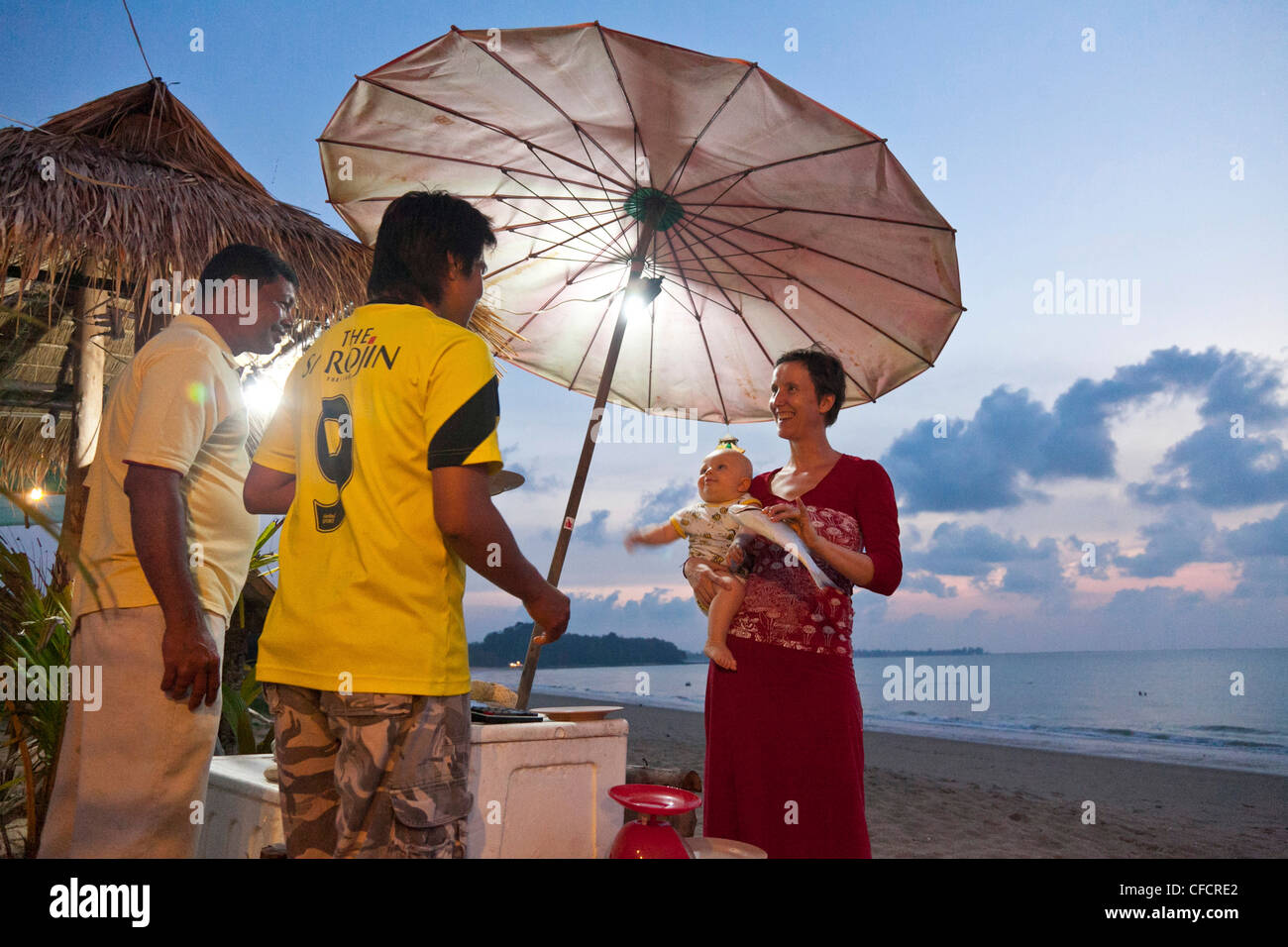 German woman with a baby on her arm buying fish from two Thai guys, beach at dusk, Pad Veek Beach, Andaman Sea, - Stock Image