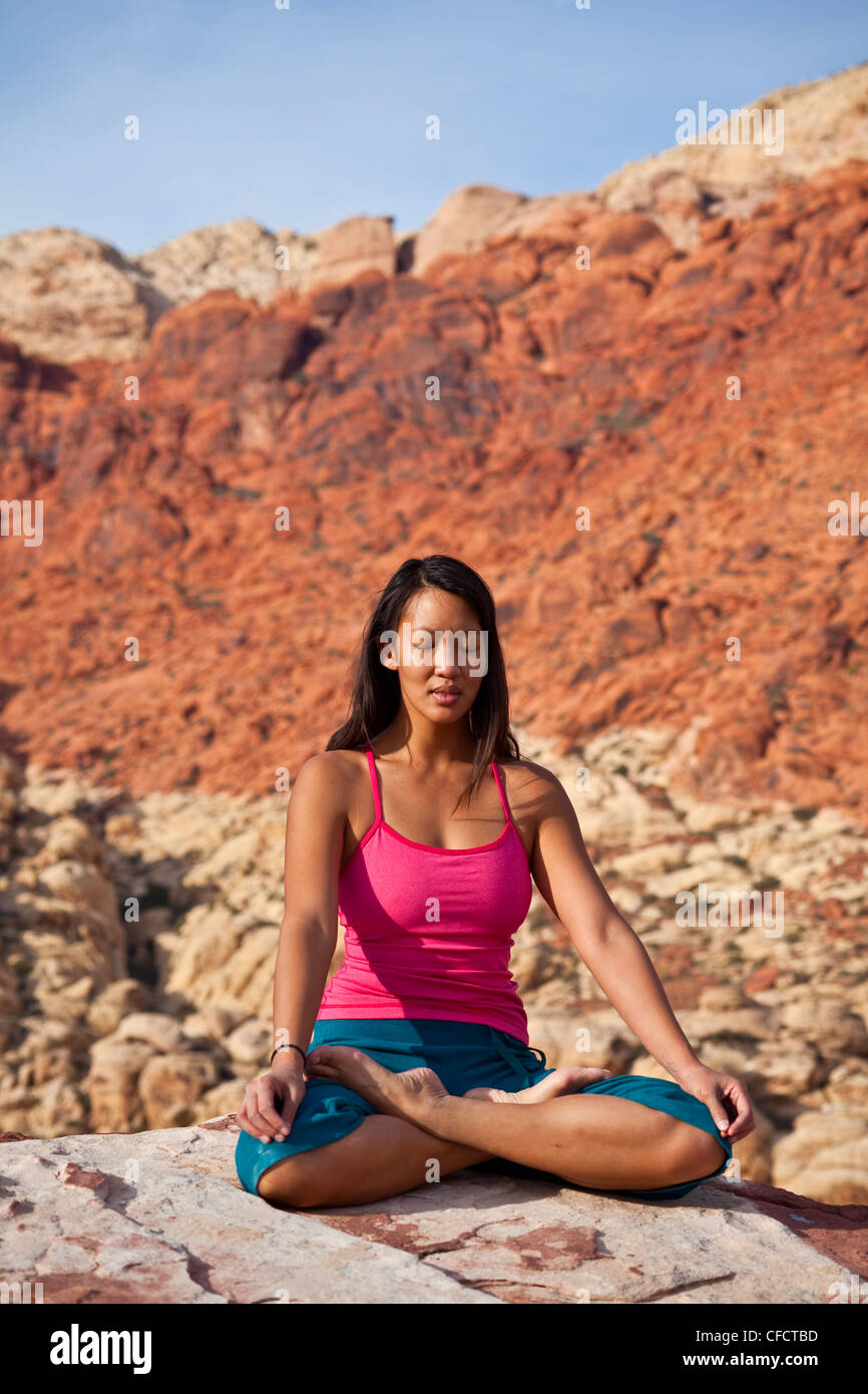 A fit young asian woman practicing yoga while on a rock climbing trip, Red Rocks, Las Vegas, Nevada, United States - Stock Image