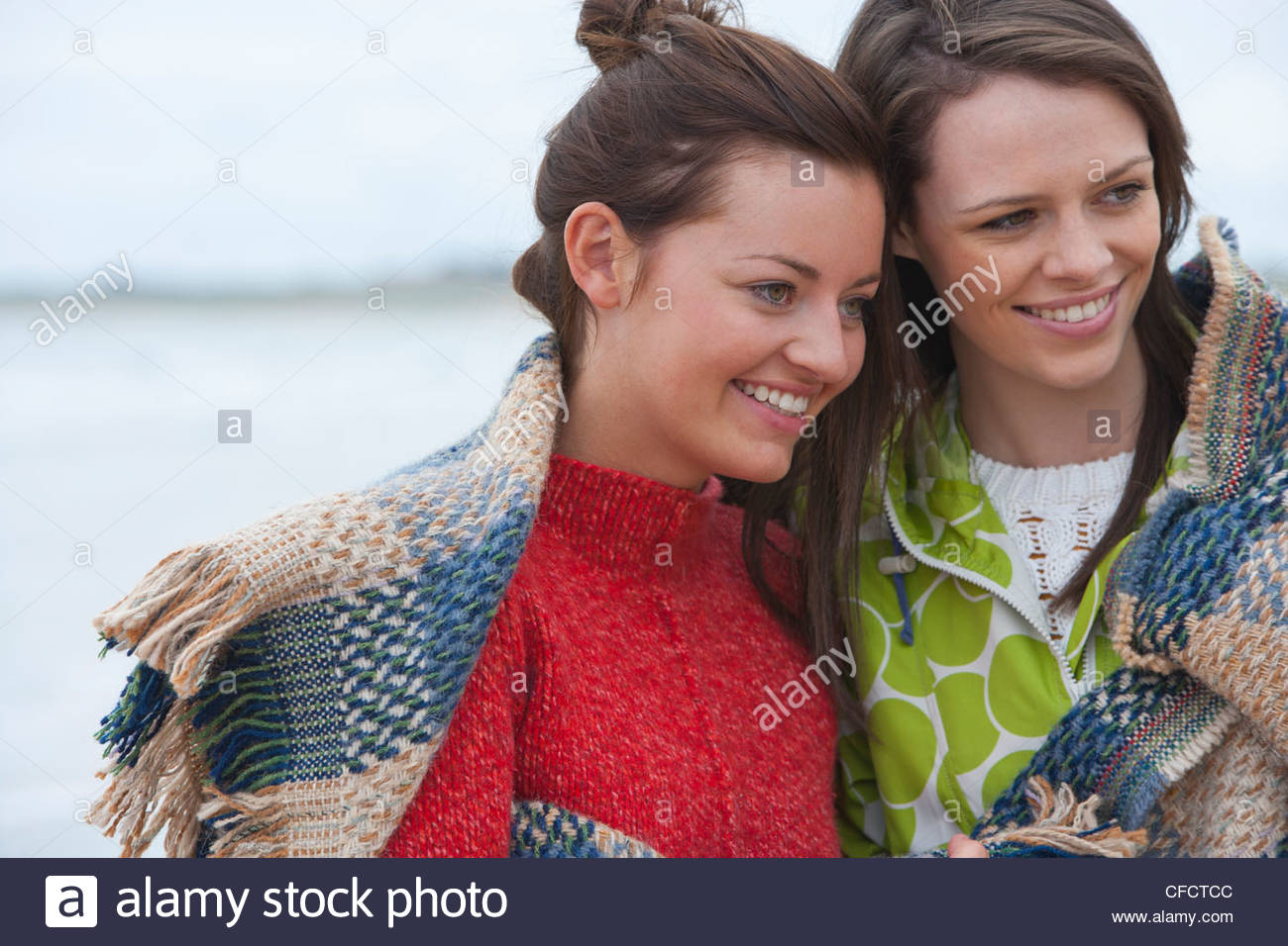 Smiling young women wrapped in a blanket on beach - Stock Image