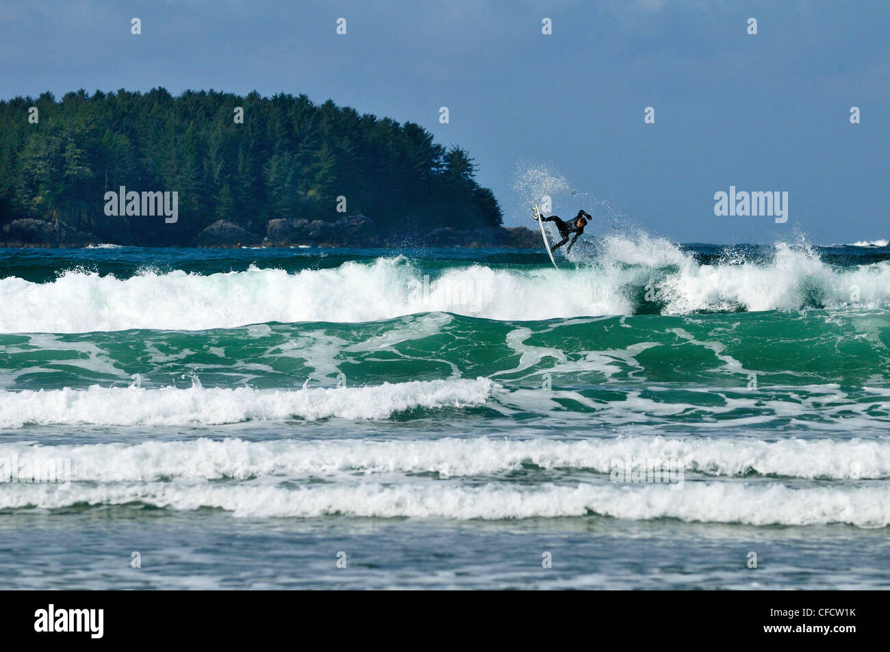 Airborne surfer on surf at Chesterman Beach in Tofino, British Columbia, Canada. - Stock Image