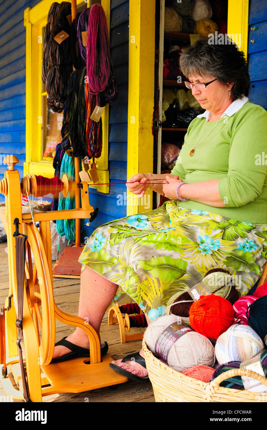 A woman, Leola Witt-McNie, (model release) plying yarn with a spinning wheel at the Whipple Tree Junction in Duncan, - Stock Image