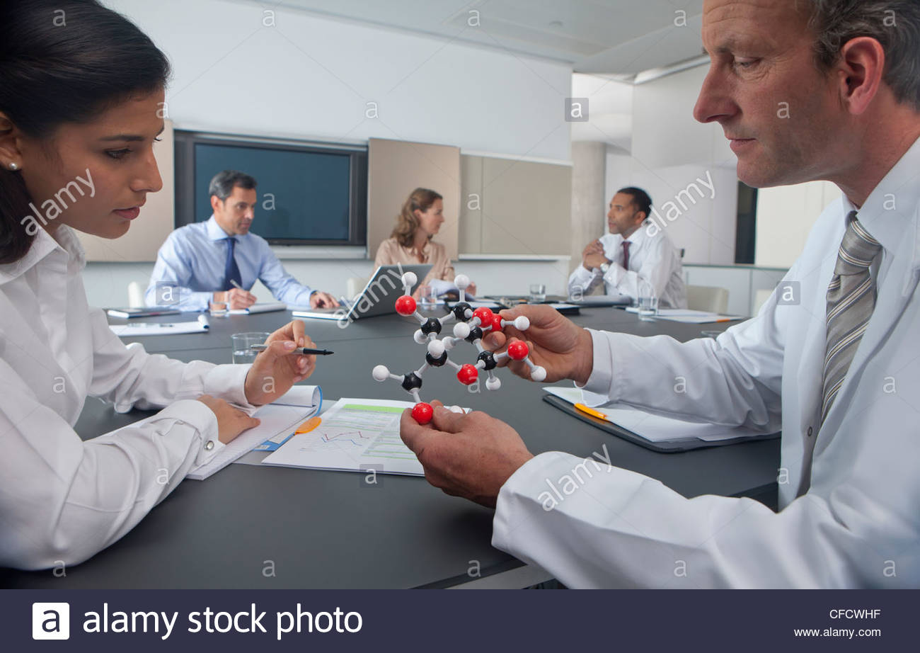 Scientist and businesswoman examining molecular model in conference room - Stock Image