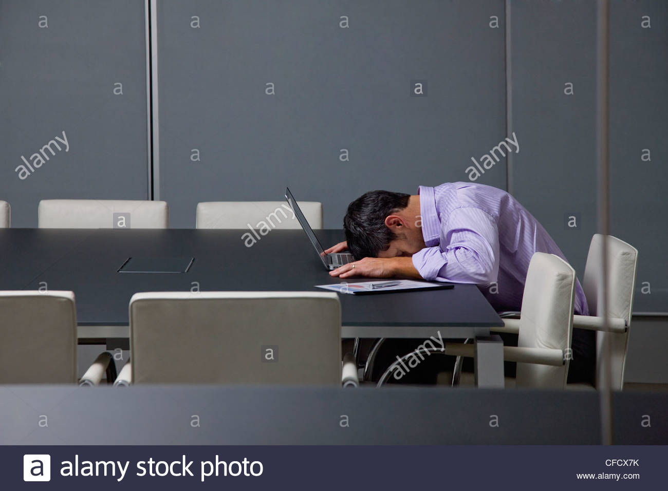 Businessman sleeping on laptop in conference room - Stock Image