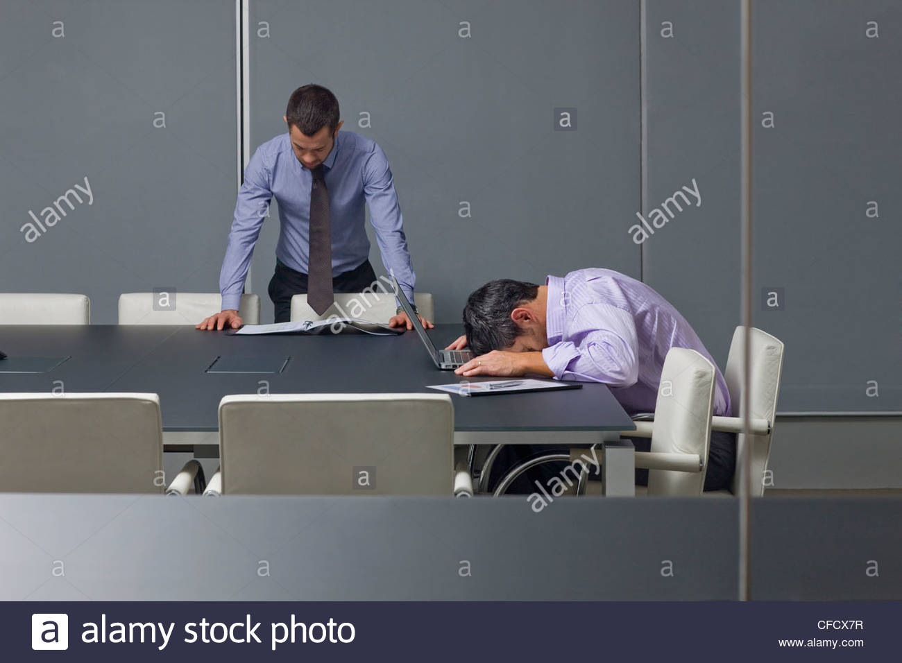 Businessman reading paperwork near co-worker sleeping on laptop in conference room - Stock Image