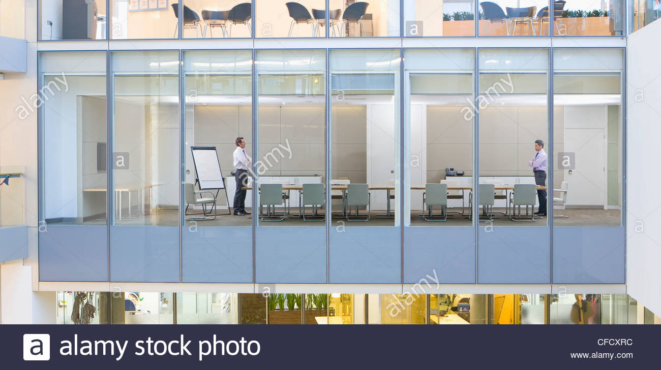 View of businessmen standing at opposite ends of conference room from outdoors - Stock Image