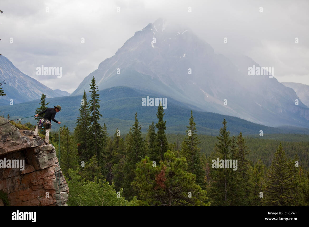 A climber preparing to rappel at Lost Boys crag with Mt Edith Cavell, Jasper National Park, Alberta, Canada - Stock Image