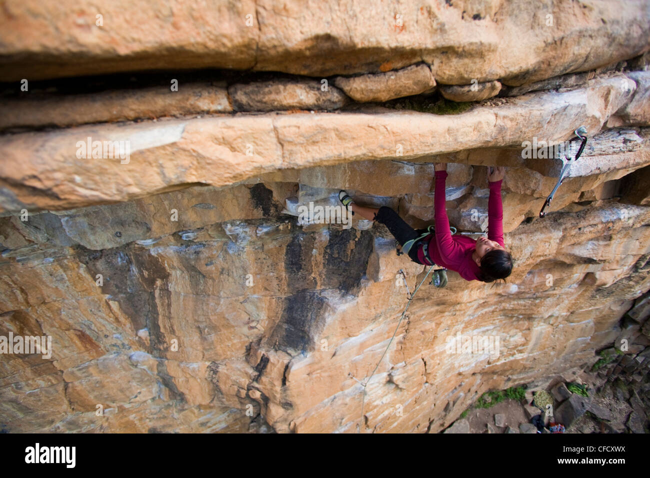 A young strong asian woman rockclimbing at Lost Boys crag in Jasper National Park, Alberta, Canada - Stock Image